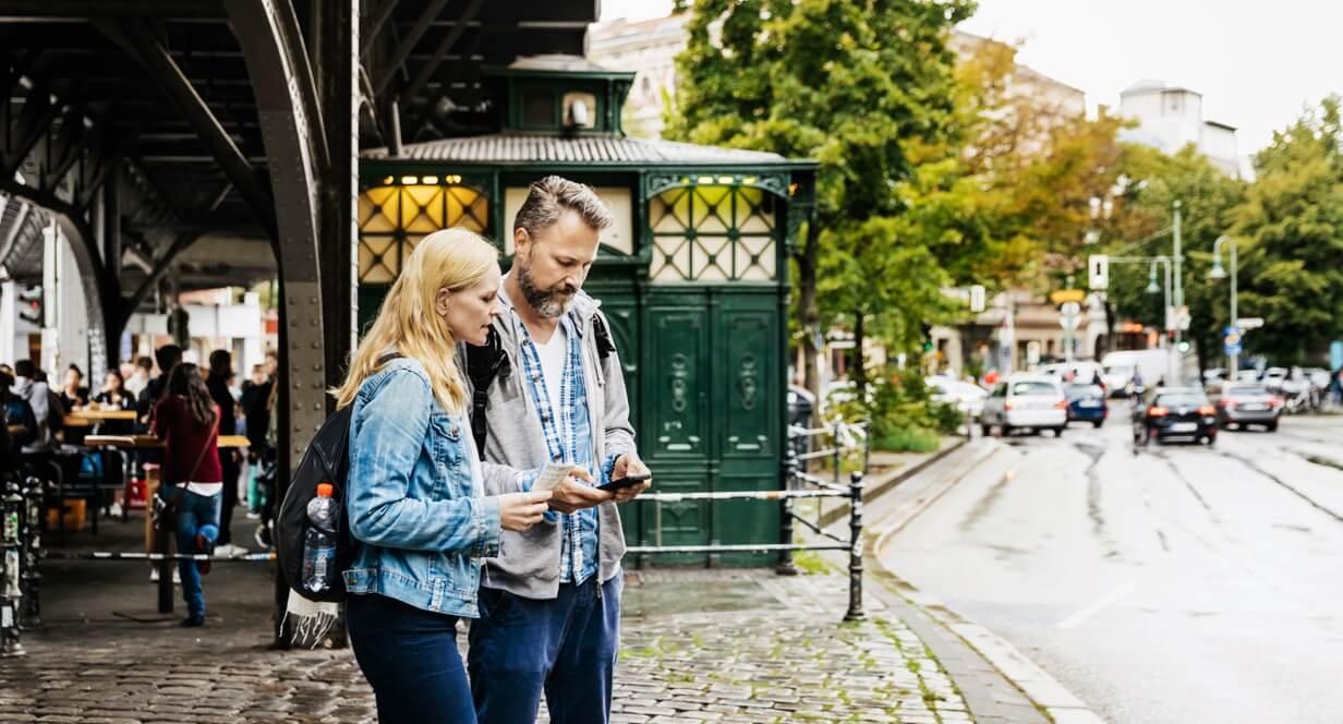 ein Mann und eine Frau stehen unter einer S-Bahnbrücke und schauen auf ein Handy.