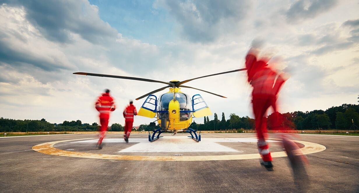 Menschen in orangefarbenen Uniformen rennen von dem Fotografen weg auf einen gelben Rettungshubschrauber zu.